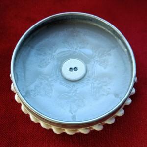Weiß verzierte runde Dose mit einem weißen Kissenknopf auf weißem Wachs, in das ein Schneekristall geprägt wurde.