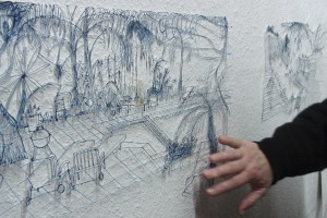 Hand drückt ausgeschnittene Zeichnung an die Wand