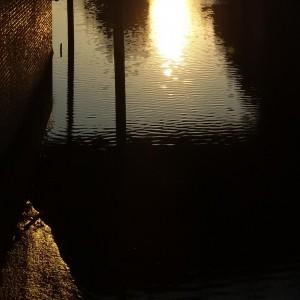 Fotografie eines Fleets, in dessen kräuselndem Wasser sich die untergehende Sonne spiegelt.