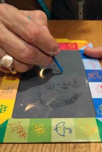 Durbahn zeichnet ein Selbstporträt auf eine Kinderzaubertafel.
