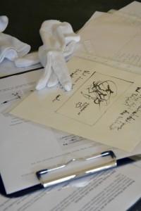 Foto weißer Handschuhe und diverser Unterlagen auf einem grünen Tisch anlässlich der Eröffnung Reihe Fleurons von EVA.