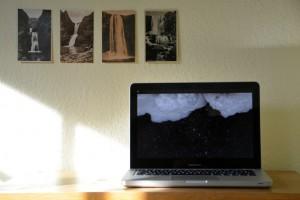 Ausstellungsansicht der Arbeit Bergfall von Sabine Höpfner. Monitor mit Videoarbeit vor Islandpostkarten von Wasserfällen.