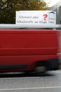Foto eines vorüberfahrenden roten Lasters vor einer Werbung zur Schimmelbekämpfung