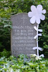 Alma de l'Aigles Grabstein in Niendorf mit Papierblume, die sämtliche falschen S- Buchstaben am Ende des Namens verdeckt
