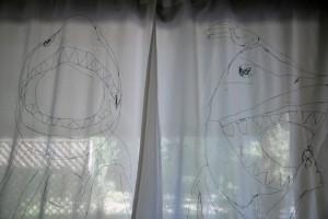 2 handbestickte Stoffe als Vorhang vor einem Laubenfenster