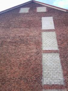 Foto eines Hauses mit zugemauerten Fenstern und Türen.