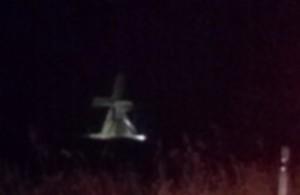 Nachtaufnahme: Foto einer geisterhaft beleuchteten Mühle am Straßenrand.