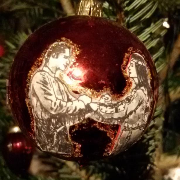 Rote Weihnachtsbaumkugel mit einer Zeichnung von Winnetous und Old Shatterhands Verblutsbrüderungspakt.