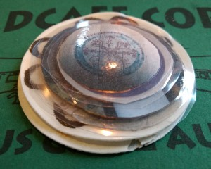 Bemalte Oblaten und rund auseschnittene und laminierte Fotos auf einer Restaurantserviette.