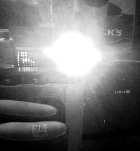 Schwarzweissfoto von einem Beamer zwischenGummistiefeln und Bierkasten
