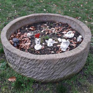 Ausgediente Engelsfiguren auf dem Friedhof Altona in einem Steinbehältnis, das an einen Brunnen gemahnt.