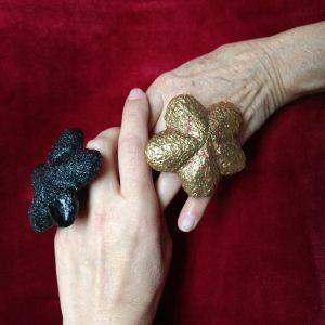 Zwei ineinandergreifende Frauenhände, eine mit großem goldenen Blumenrin, eine mit großem schwarzen Ring vor einem Hintergrund aus rotem Samt.