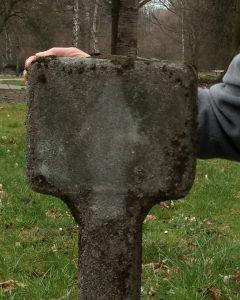 EVAs Hand auf der alten Poststeinruine mit dem Marienumriss.