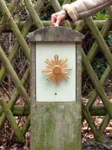 Bettinas Hand lässt einen goldenen Heiligenschein aus Plastik vor einer gut erhaltenen Poststeinruine schweben.