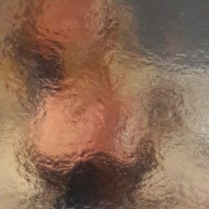Spiegelung eines Gesichts auf einer Goldpappe, Anmutung wie Wasseroberfläche oder Brunnen. Foto von Bettina Ulitzka-Allali.