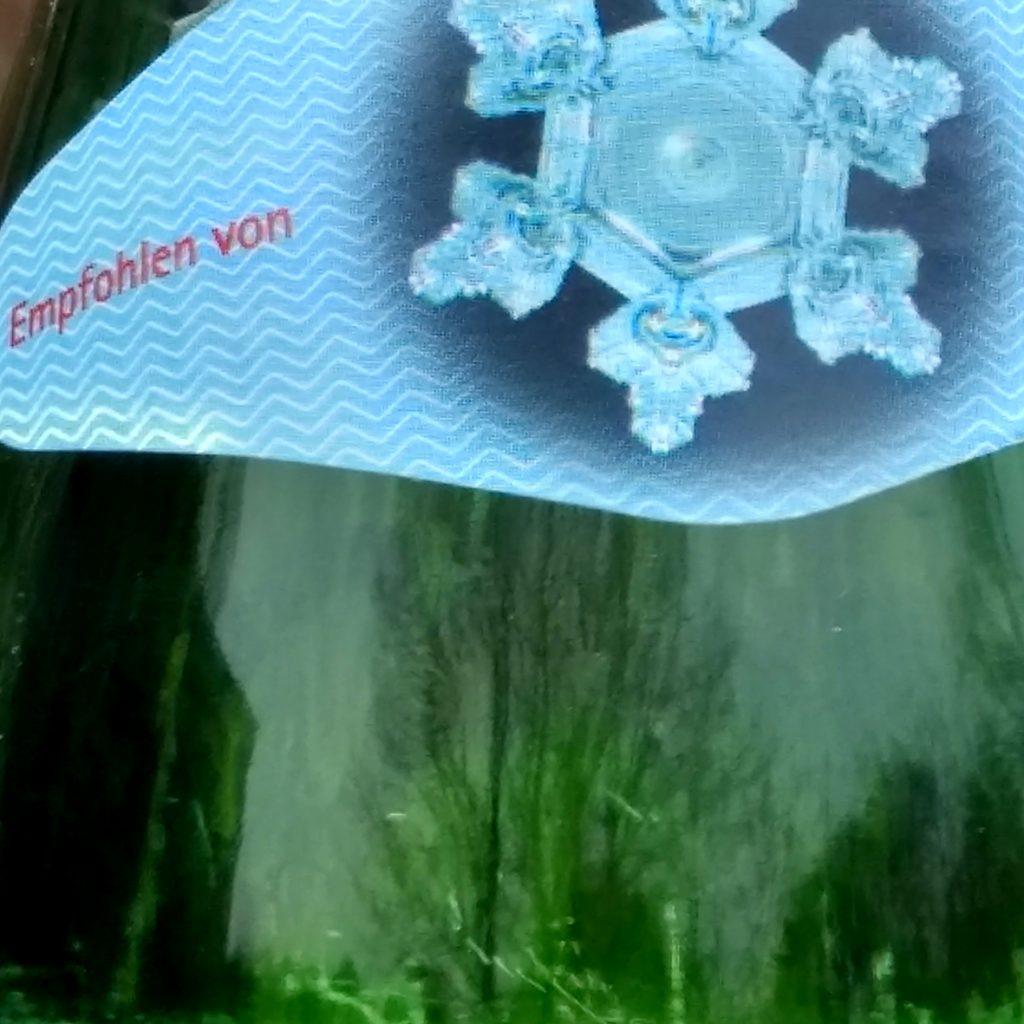 Ein Frühlingsgarten spiegelt  sich im grünen Glas einer Wasserflasch, auf deren Etikett eine Schneeflocke prangt.