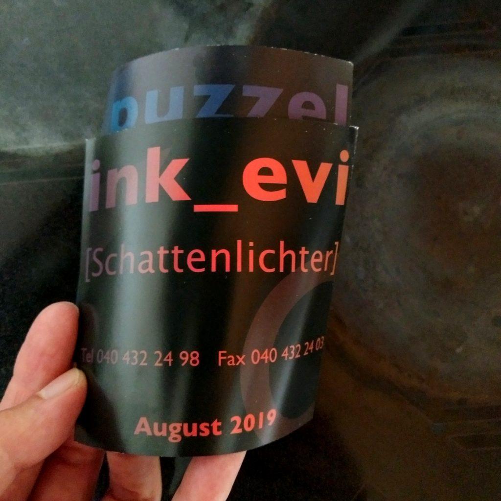 EVAs Hand mit dem dunklen Flyer von Puzzelink