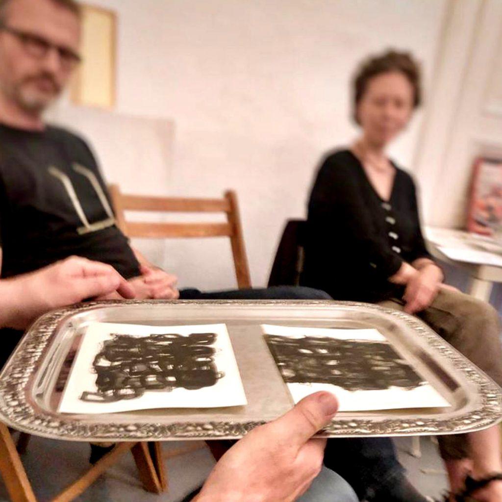 Salon Waldeinsamkeit bei puzzelink, Zeichnungen der Künstlerin EVA werden auf einem Silbertablett umhergereicht.