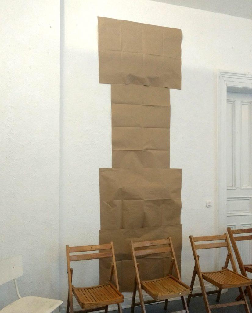 Ausstellungsraum mit Stuhlreihe, dahinter bis zur Decke ein mit Packpapier abgeklebter Bereich