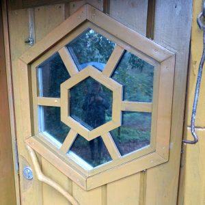 Hüttentür, in deren Glasfenster sich Bettina spiegelt