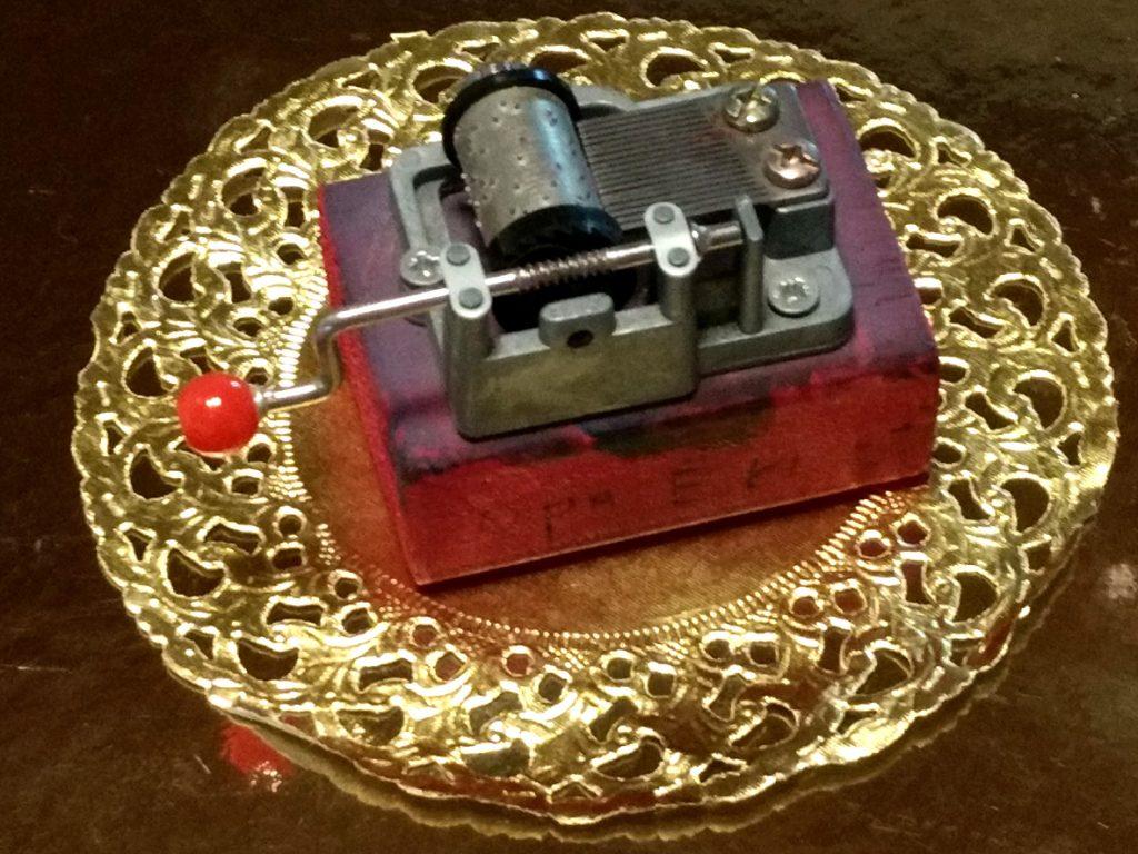 Minidrehorgel auf bemaltem Holzklotz mit Schriftzug Opa Ernst, präsentiert auf einem goldenen Papieruntersetzer
