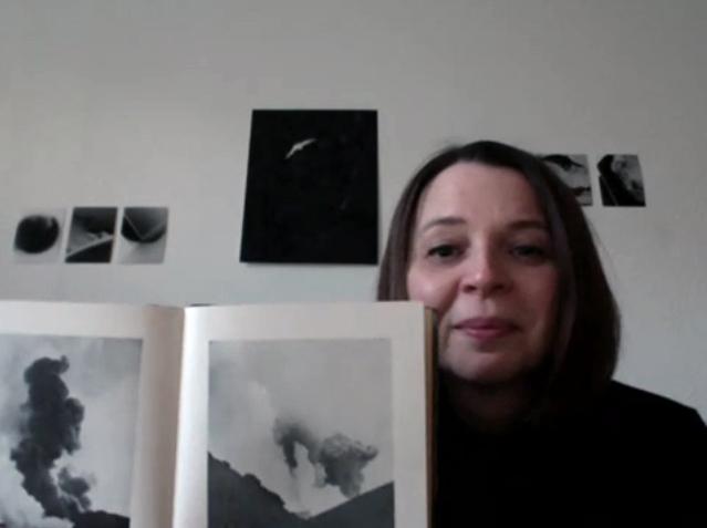 Sabine Höpfner mit dem Buch Heklugos vor einer Wand miteigenen Fotos aus Island