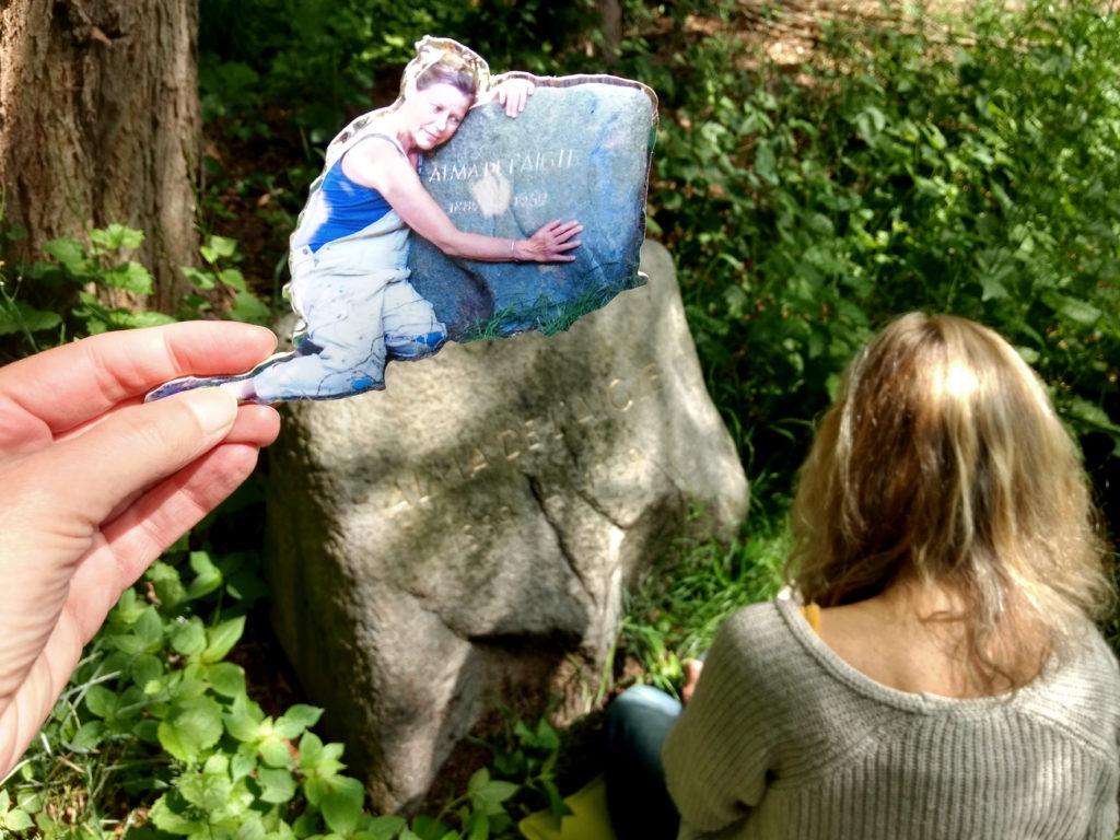 Die Hamburger Künstlerin Bettina Ulitzka-Allali vergoldet die Buchstaben auf Almas Gedenkstein im Mai 2020 und EVA hält ein Laubsägeobjekt mit einem Foto von Bettina ins Bild, wie sie nach der ersten Goldaktion den Stein umarmt.