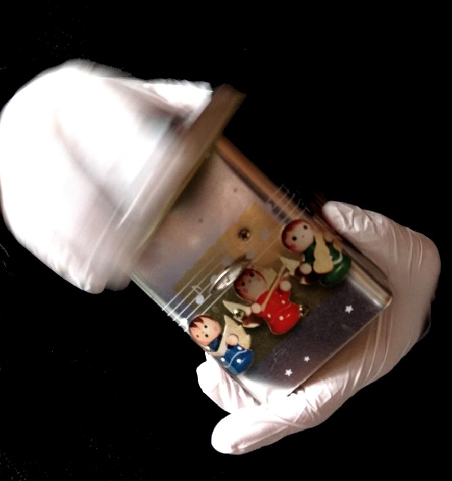 Weihnachtliche Gebäckdose mit integrierter Spieldose in den gummibehandschuhten Händen der Hamburger Künstlerin EVA.