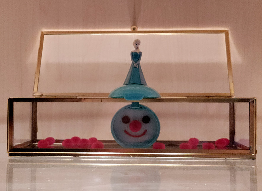 Plastikprinzessinnendose mit Clownsgesicht in der geöffneten Dose, aufgestellt in einem Glaskasten, umgeben von 12 roten Minibommeln